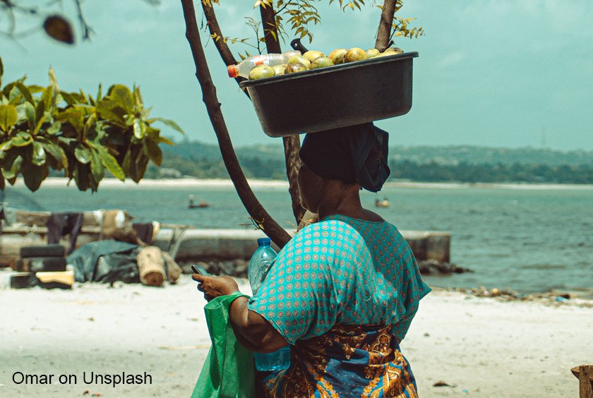 woman with basket on her head with beach behind her